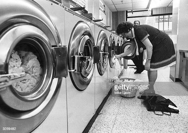 A woman empties a washing machine in a laundrette
