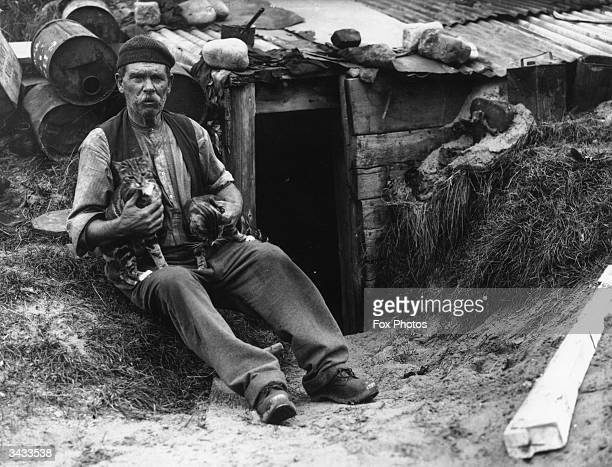 Ex-miner Ben Evans and his two pet cats outside his home in the sandhills between Porthcawl and Aberavon, where he lives as a hermit. He is known as...