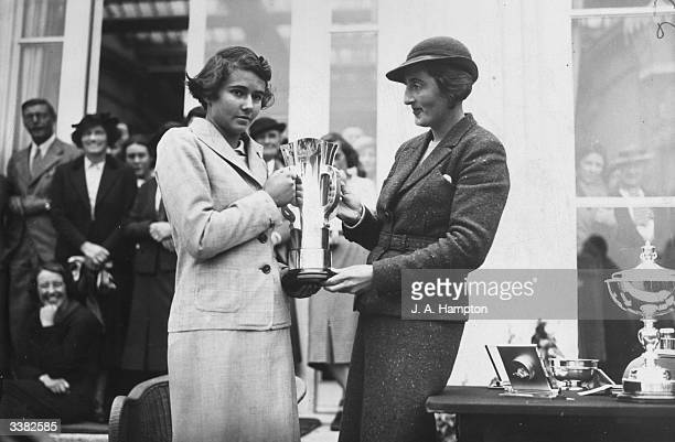 Enid Wilson who won the British Amateur Open presenting the cup to Mlle Vagliano of France winner of the Girl's Open Golf Championships at Stoke...