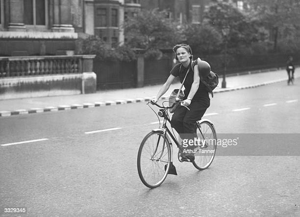A young girl on a bicycle ride carrying her tinhat and gasmask