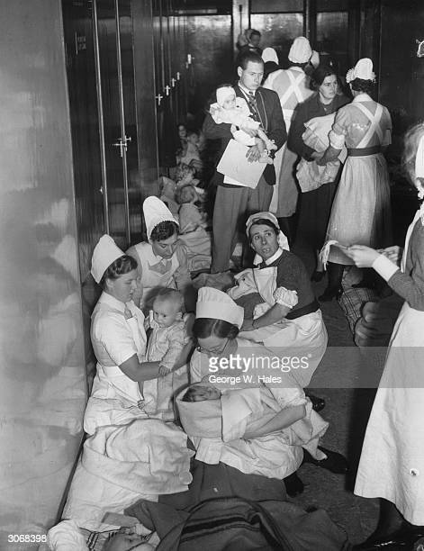 A doctor and nurses move their young patients into a corridor after a London children's hospital was struck by Nazi bombs during a World War II air...
