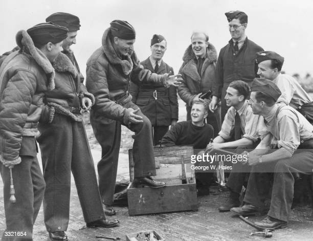 A group of RAF bomber pilots give a firsthand account of their last bombing raid to some of the maintenance staff who load the bombs which the pilots...