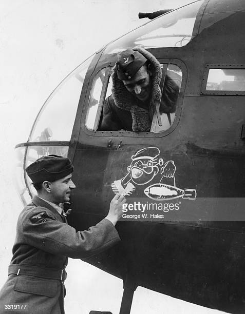 A member of the ground maintenance staff at an RAF station adding a bomb to a cartoon of Popeye drawn on a Hampden bomber plane