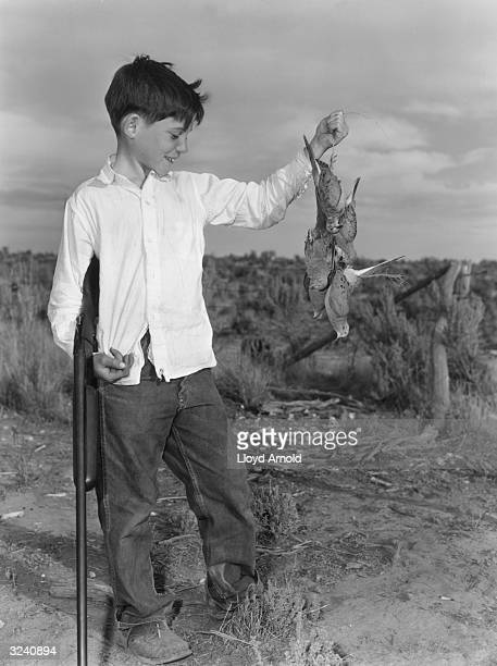 Gregory Hemingway youngest son of writer Ernest Hemingway smiles while holding a clutch of dead doves and a gun Idaho