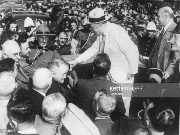British prime minister Winston Churchill shakes hands with a Quebec City official as Canadian prime minister Mackenzie King looks on with a smile,...