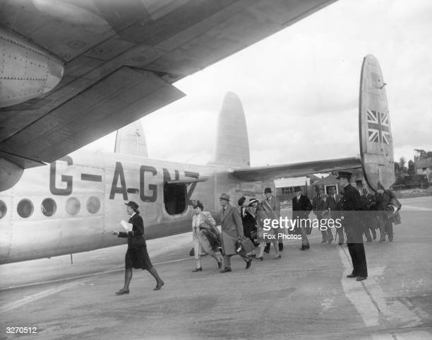 A traffic clerk employed by the British Overseas Airways Corporation leads passengers aboard a York aircraft bound for South Africa at Heathrow...