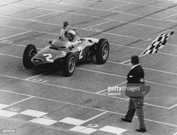 American racing driver Phil Hill crosses the finishing line in his Ferrari winning the Italian Grand Prix at Monza, Milan. In the same race German...