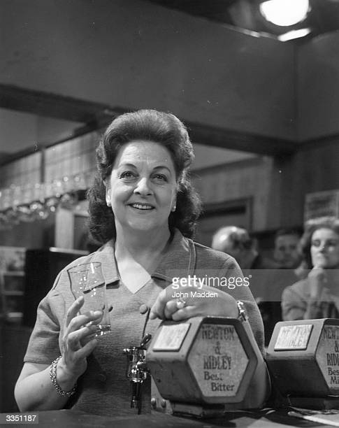 Actress Betty Driver as barmaid Betty Turpin serving behind the bar at the Rover's Return pub in the television soap opera 'Coronation Street'