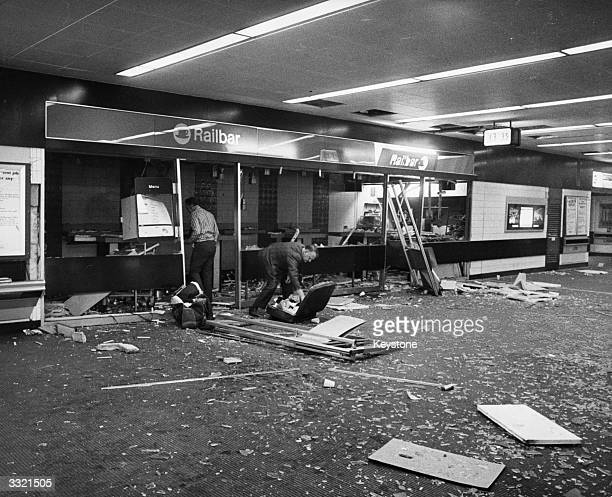 A plain clothes police officer examines a suitcase on the floor of the concourse at Euston Station London in front of the devastated Railbar where a...