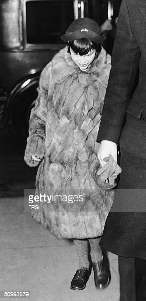10yearold American heiress Gloria Vanderbilt walks from her car to her mother's house New York New York January 12 1935 She is dressed in a gray...