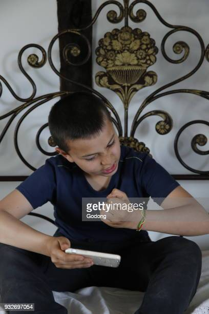 10yearold boy playing with a cell phone France