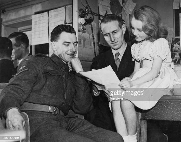Year-old British actress and singer Petula Clark goes over a script with Cecil Madden of Empire Broadcasting and her father, Lance Corporal Leslie...