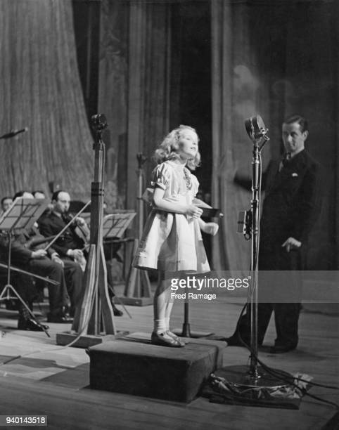 Year-old British actress and singer Petula Clark performs at the BBC's Empire birthday party, watched by bandleader Geraldo , December 1942.