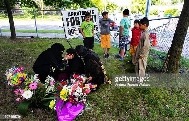 10yearold Hamza Malik brother of 13yearold Bakhtawar Malik looks on at a makeshift memorial with his mother Farah Ejaz at the scene where a car...