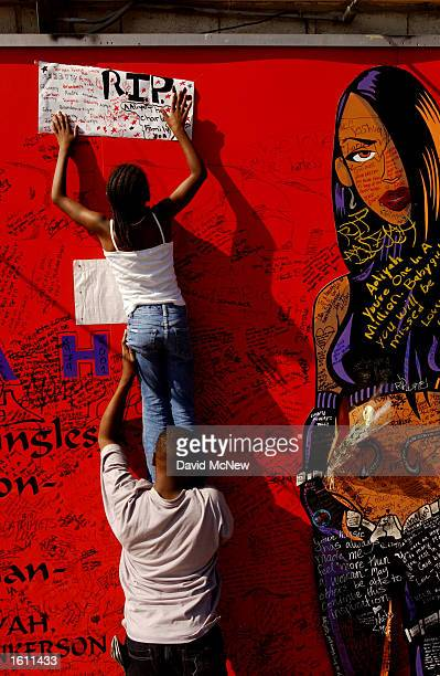 10yearold Ravyn Charles top and her brother 15yearold Joshua hang a card on a billboard for the late singer and actress Aaliyah August 28 2001 on...