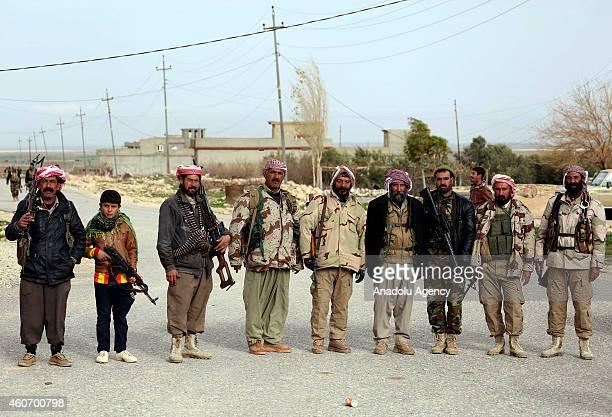 10yearold Yazidi boy holding AK47 poses with Yazidi men and Peshmerga fighters near the shrine of Yazidi Sheikh Serafettin with Yazidi men on Sinjar...