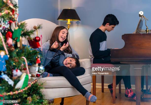 10-years-old girl, a sister, plating with her 5-years-old brother near by the decorated christmas tree when their older brother playing piano in the backdrop. - 10 11 years stock pictures, royalty-free photos & images