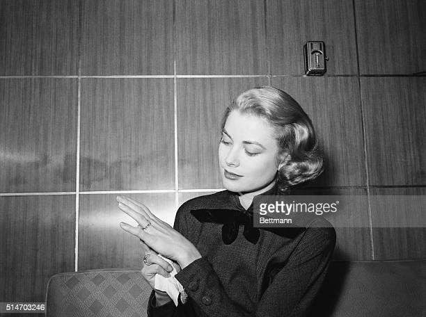 Film actress Grace Kelly en route to Hollywood for movie work strikes a pose to show off the engagement ring given her by Prince Rainier III of...