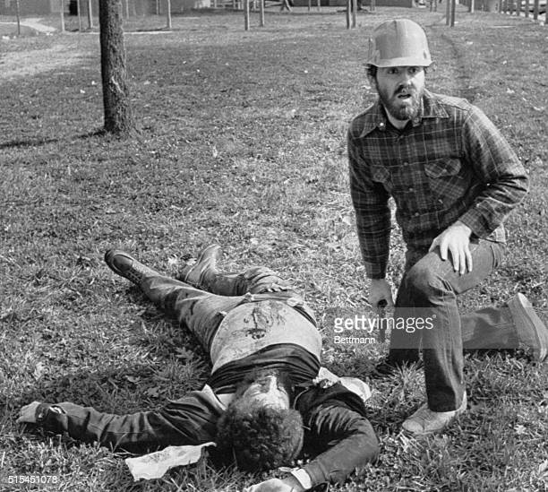 Greensboro, North Carolina- A pistol-carrying comrade kneels beside a slain member of the Communists Workers Party, Nov.4 only moments after a...