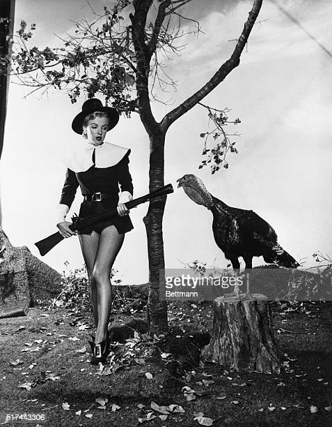 Hollywood California Wearing a costume that is halfPuritan halfchorine pretty Marilyn Monroe seems to have little desire to hunt turkey after finding...