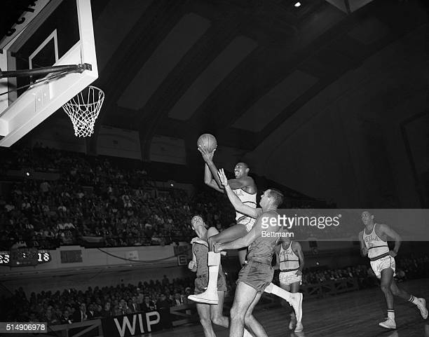 Philadelphia PA Warrior Wilt Chamberlain wades through New York Knickerbockers' Carl Braun and Charlie Tyra during a nip and tuck scoring battle...