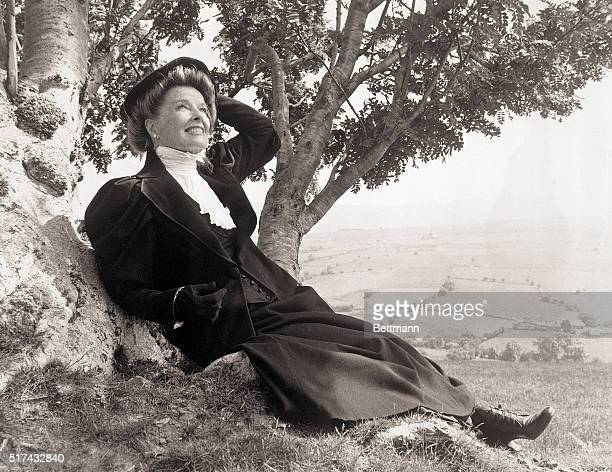 North Wales, United Kingdom-With the lush green fields of valley in Wales in the background, Katharine Hepburn sits on a hillside during a pause in...