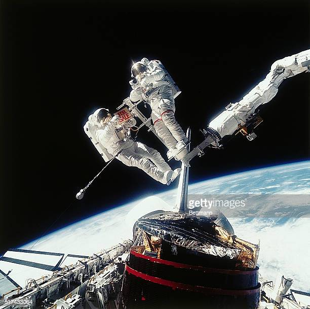 Earth Orbit Astronaut Dale A Gardener and Astronaut Joseph P Allen stand on the remote arm of the Space Shuttle Discovery which has just captured a...