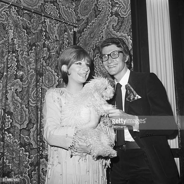 New York NY Barbara Streisand star of Funny Girl holds up her dog Sadie to meet famous French dress designer Yves St Laurent in Barbara's dressing...