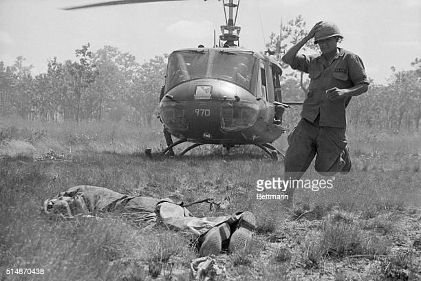 Plei Me South Vietnam A soldier of the US Cavalry rushes to pick up an American body as a waiting helicopter prepares to take off under heavy fire...