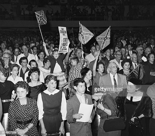 New Orleans LA Waving Confederate flags two small children stand on chairs as they join adults in attending a meeting of the White Citizens Council...
