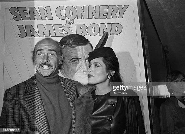 """Paris, France- Actor Sean Connery and actress Barbara Carrera, posing 11/16 in front of a poster promoting the new James Bond film """"Never Say Never..."""