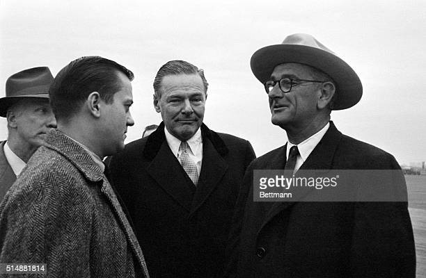 Wearing a Western hat Sen Lyndon Johnson talks to newsmen on arrival at LaGuardia Airport here Nov 16th On hand to welcome him is US Ambassador to...