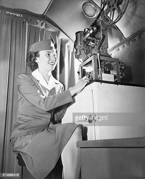 Flight stewardess Isle Berger of Pan American World Airways shows the first fulllength sound movies to passengers aboard a Transatlantic Clipper This...