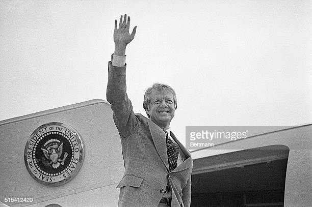 Washington, DC-: President Carter, shown waist-up, waves as he boards a helicopter on the White House lawn to fly to Camp David, Maryland, where he...