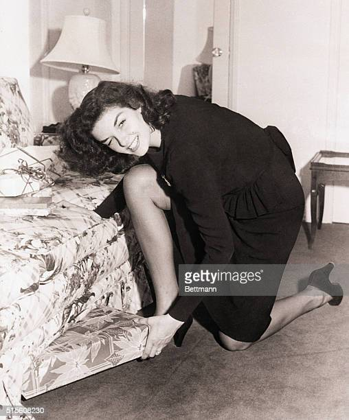 Hollywood CA Screen star Jane Russell gently hints that Christmas is approaching a she hides a present for someone under the bed