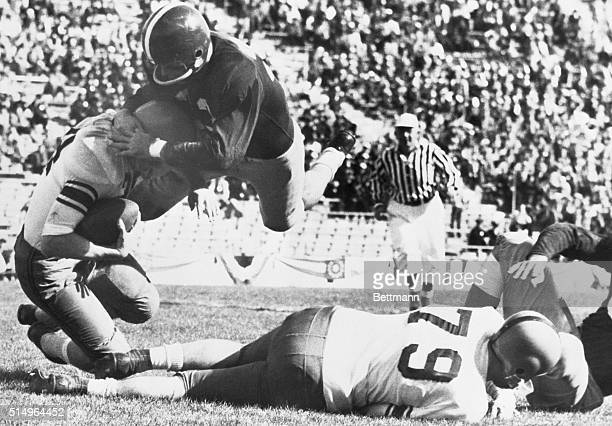 Dallas, TX- TCU halfback, Jim Swink, puts a diving headlock on Syracuse's Fred Kuczala, who picked up three yards late in the second quarter of the...