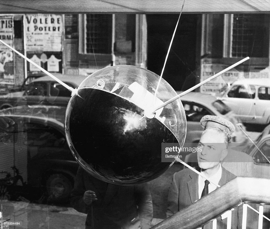 Rome, Italy- A man observes a model of Russia's Sputnik #1, on display in a Rome department store.