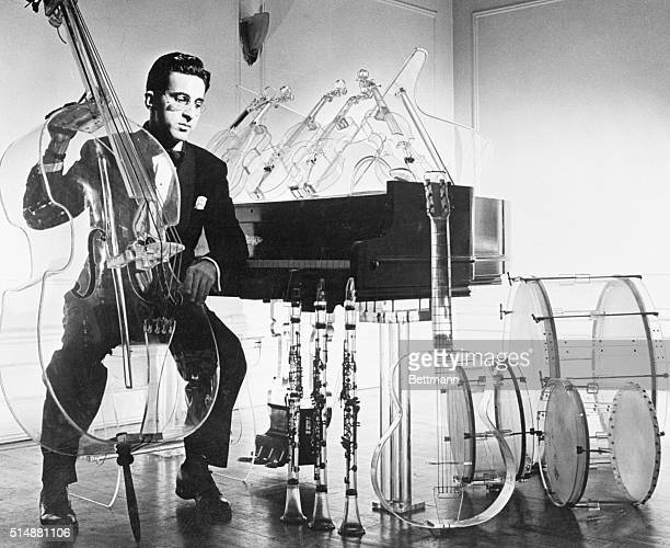 Ghostlylooking musical instruments surround musician Billy Glass who made them as a hobby in less tan a year's spare time using his home cooking oven...