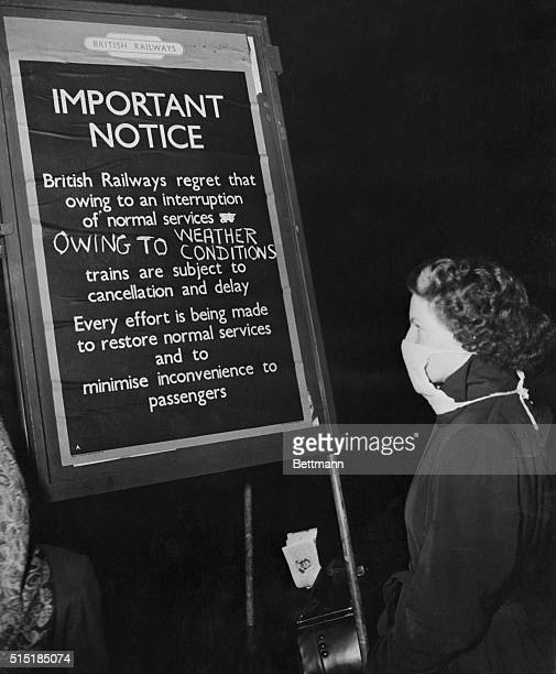 London, England: A young woman in London, wearing smog mask, reads of train delays due to smog conditions.
