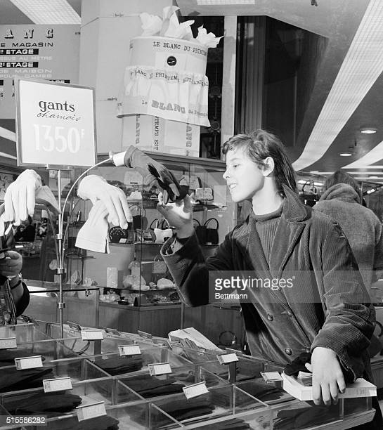 Examining some gloves in a Paris department store this young shopper is wholly unaware of close scrutiny from the eye of a hidden television camera...