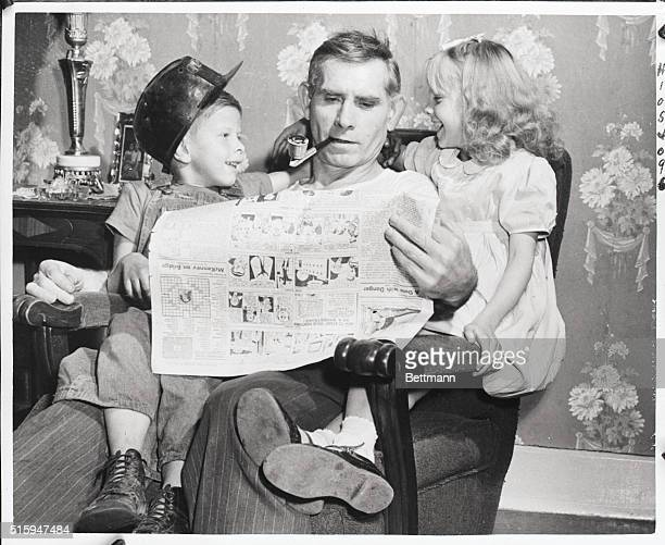 """Castel Shannon, PA: A miner for 37 years, John Stutt, of Castel Shannon, uses his """"Idel time"""" to read the """"funnies"""" to his granchildren, """"Butchie""""..."""