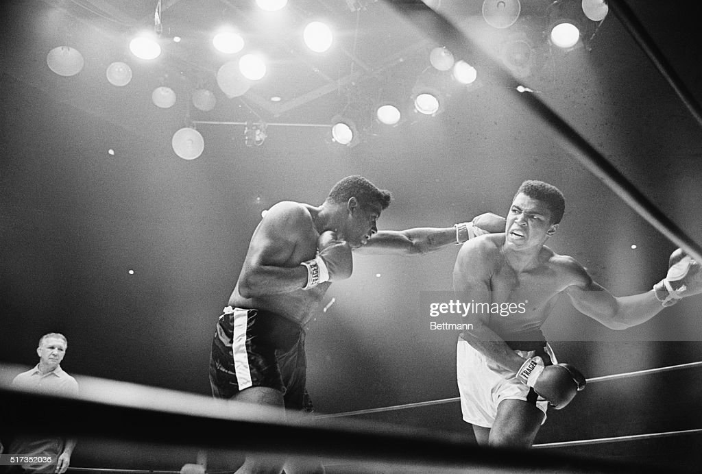 Las Vegas, NV- A snarling Cassius Clay (R) ducks under a long left jab by former champion Floyd Patterson, in the Las Vegas Convention Center during the sixth round of their scheduled 15-round title bout. Clay bounced back to deck the 30-year-old Patterson later in the round for a mandatory eight count.