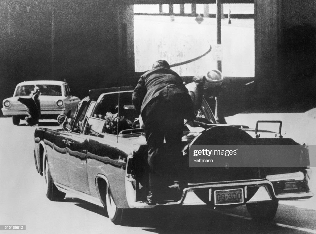 Assassination of President Kennedy. Mrs. Kennedy leans over dying President as a Secret Service man climbs on back of car.