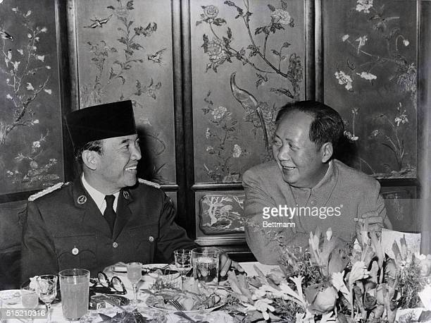 Peiping China President Dr Sukarno of Indonesia left is seen chatting with Chairman Mao TseTung of the People's Republic of China during a banquet...