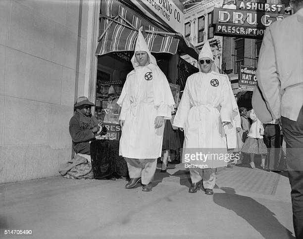 Montgomery AL Elderly Negro news vendor appears unconcerned as robed Knights of the Ku Klux Klan stroll downtown street here 11/24 The informal walk...