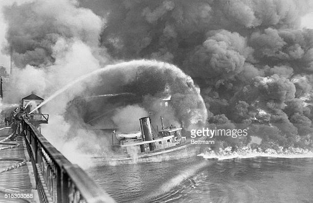 11/3/1952ClevelandOH Firemen stand on a bridge over the Cuyahoga River to spray water on the tug Arizona as a fire started in an oil slick on the...