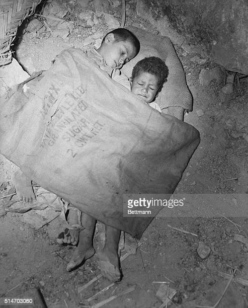 Amman, Trans-Jordan: These young Arabs share a sack in an effort to protect themselves from the elements. They are part of a large group of...