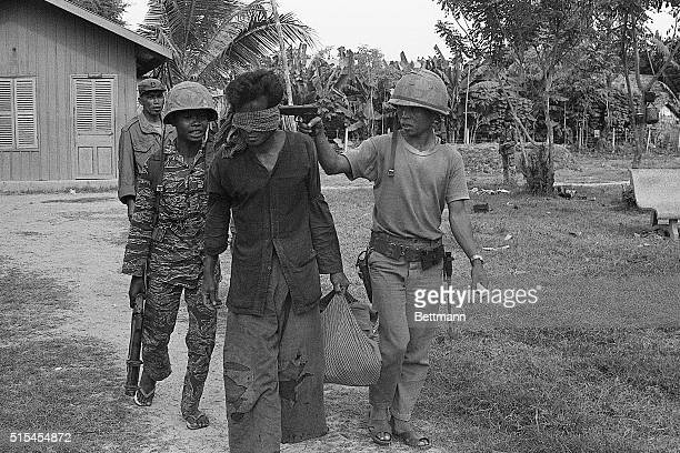 11/4/1973Prek Thong Cambodia Pointing a 45 at the head of a blindfolded Khmer Rouge suspect a Cambodia officer walks him toward a command post for...