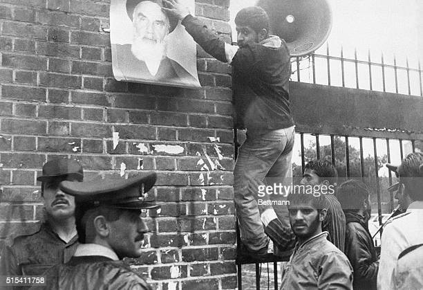 Tehran, Iran- A Moslem revolutionary puts up a poster of Ayatollah Khomeini on the outer wall of the U.S. Embassy compound, occupied 11/4 by students...