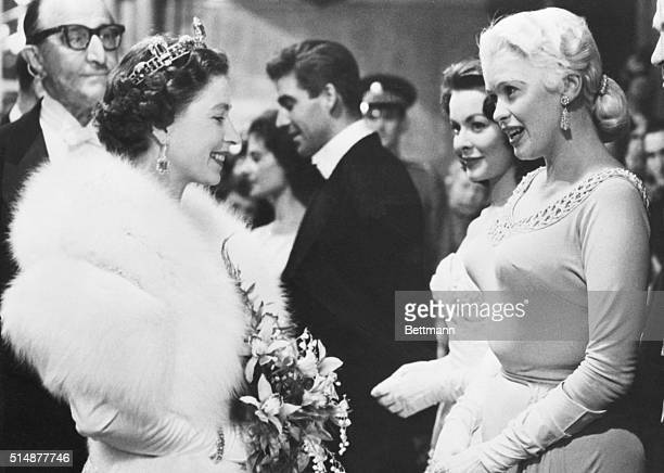 London, England: American actress Jayne Mansfield and England's Queen Elizabeth II are shown chatting on the reception line during the Royal Command...